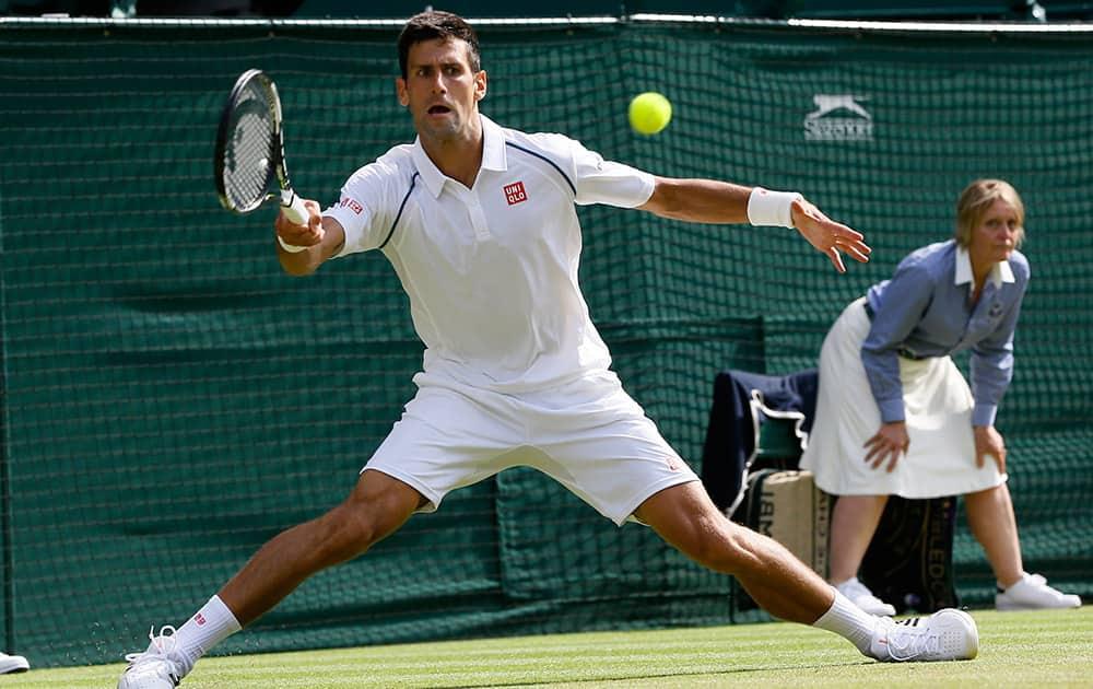 Novak Djokovic of Serbia returns a ball to Bernard Tomic of Australia during their singles match at the All England Lawn Tennis Championships in Wimbledon, London.