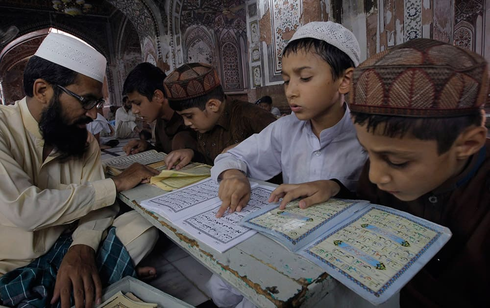 Pakistani children learn to read the Quran at a mosque during the month of Ramadan in Peshawar, Pakistan.