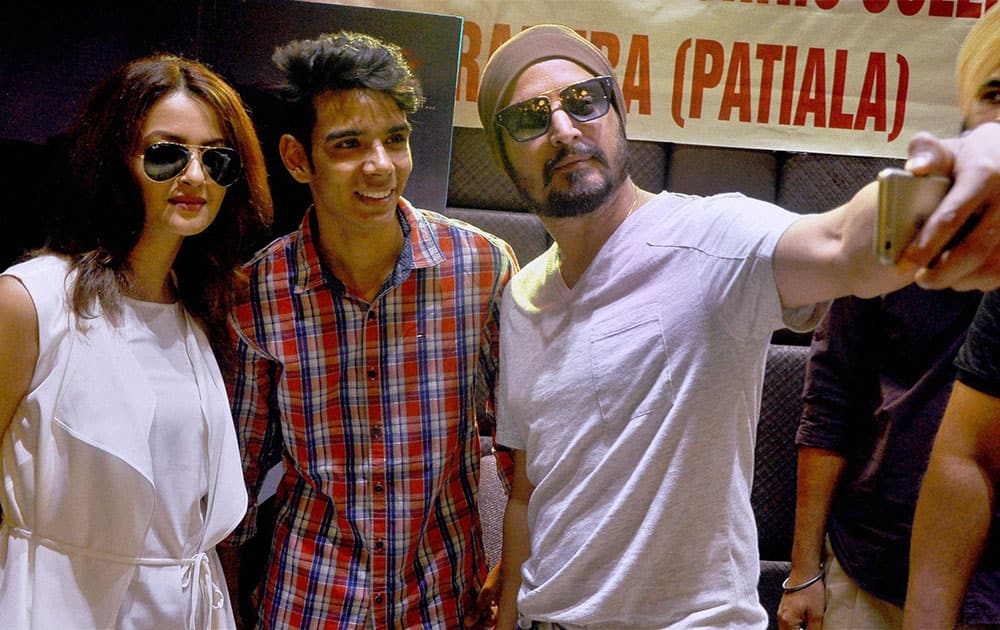 Bollywood actor Jimmy Shergill and actress Surveen Chawla take a selfie with a fan at an event to promote their upcoming movie in Patiala.