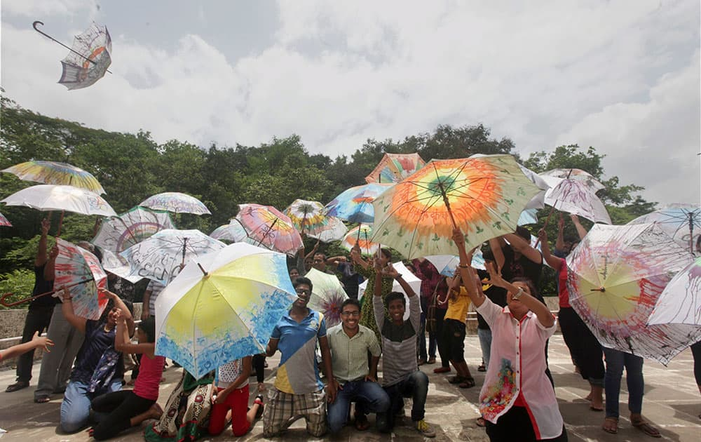 People take part in an Umbrella Workshop where people paint umbrellas with colors in Navi Mumbai.