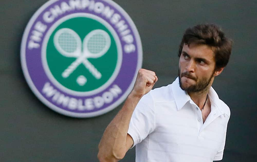 Gilles Simon of France celebrates after winning the third set against Gael Monfis of France during their singles match at the All England Lawn Tennis Championships in Wimbledon, London.