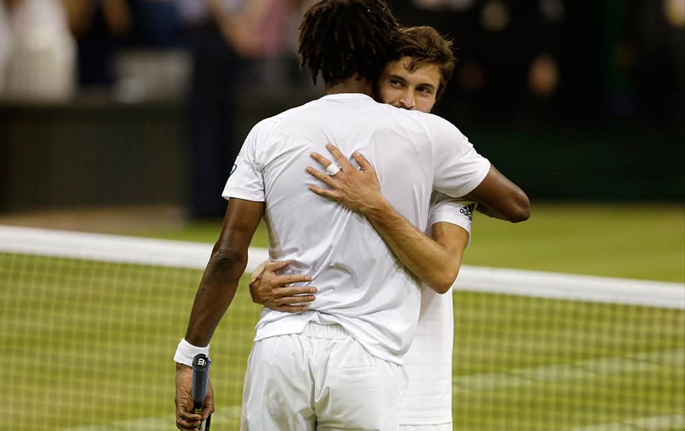 Gilles Simon of France, right, embraces Gael Monfils of France after winning the singles match at the All England Lawn Tennis Championships in Wimbledon, London.
