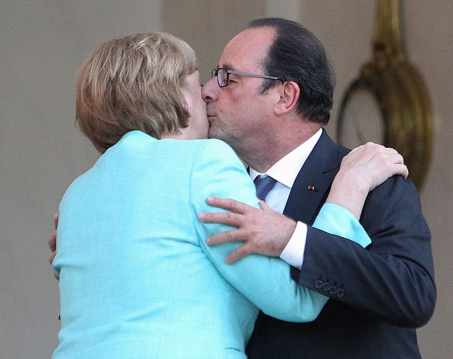 France's President Francois Hollande, right, kisses German chancellor Angela Merkel after a diner, at the Elysee Palace, in Paris, France.