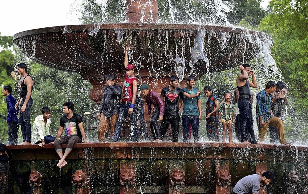 People beat the heat under a fountain in New Delhi.