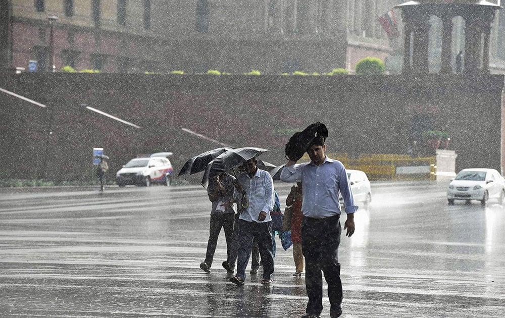 People walk in rains at Vijay Chowk in New Delhi.
