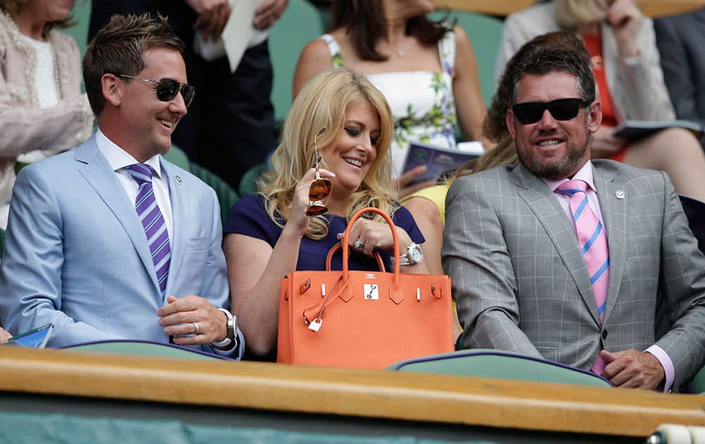 Golfer Ian Poulter, his wife Katie and fellow golfer Lee Westwood, take their seats prior to the start of the singles match between Serena Williams of the United States and Venus Williams of the United States, at the All England Lawn Tennis Championships in Wimbledon, London.