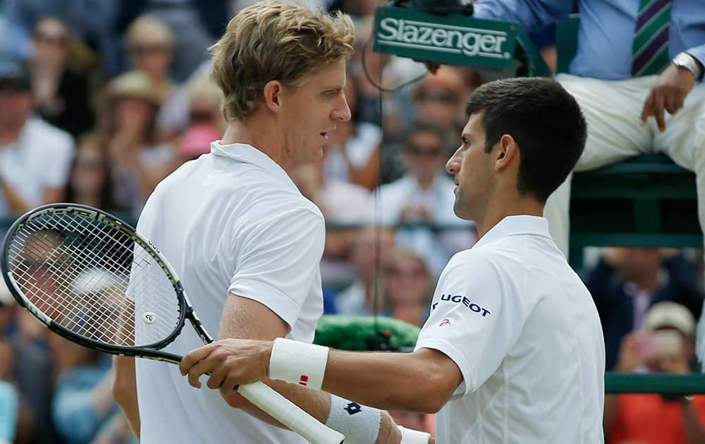Novak Djokovic of Serbia shakes hands at the net with Kevin Anderson of South Africa, after winning their singles match, at the All England Lawn Tennis Championships in Wimbledon, London. Djokovic won 6-7, 6-7, 6-1, 6-4, 7-5.
