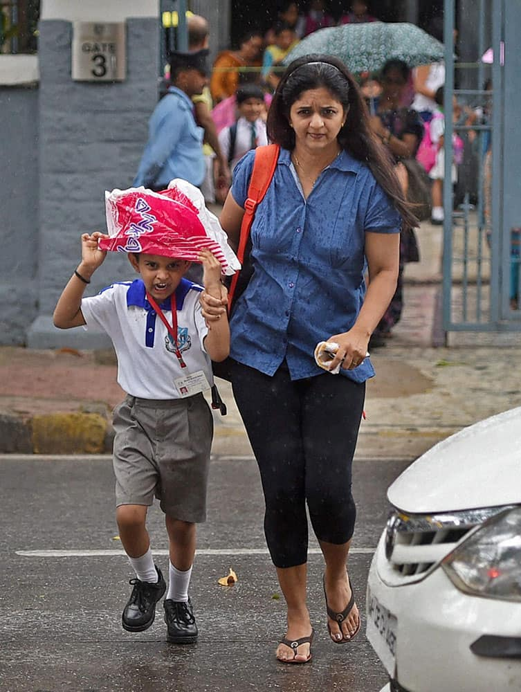 A school boy along with his mother runs for shelter as it rains in Mumbai.