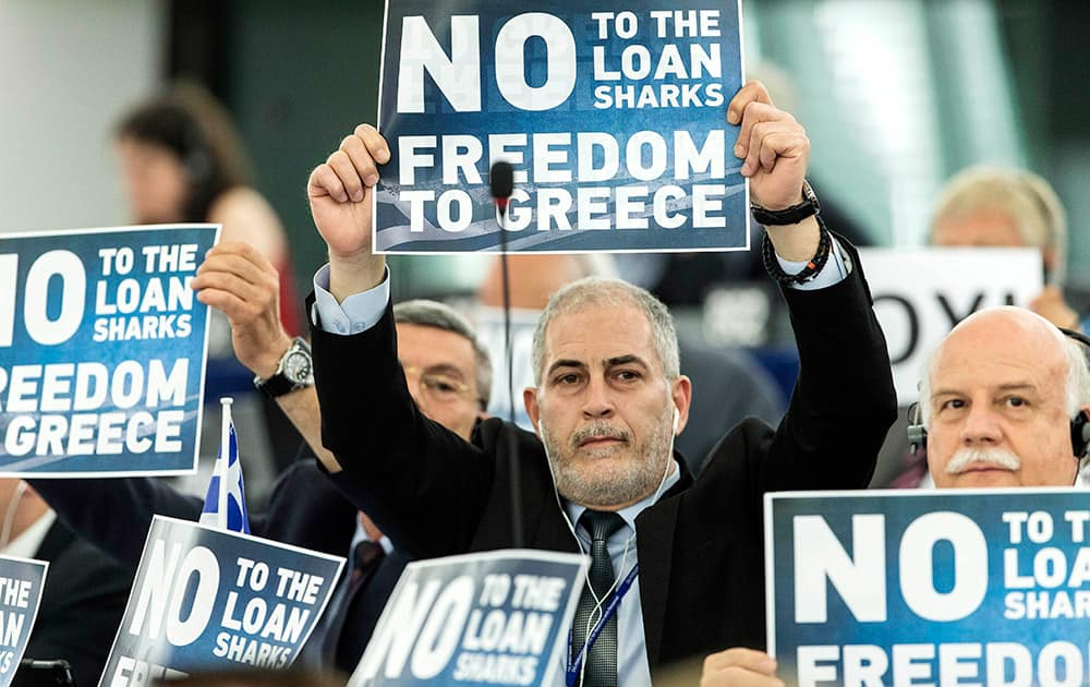 Far-right E.U Parliament members display posters before Greek Prime Minister Alexis Tsipras delivers his speech at the European Parliament in Strasbourg, eastern France.