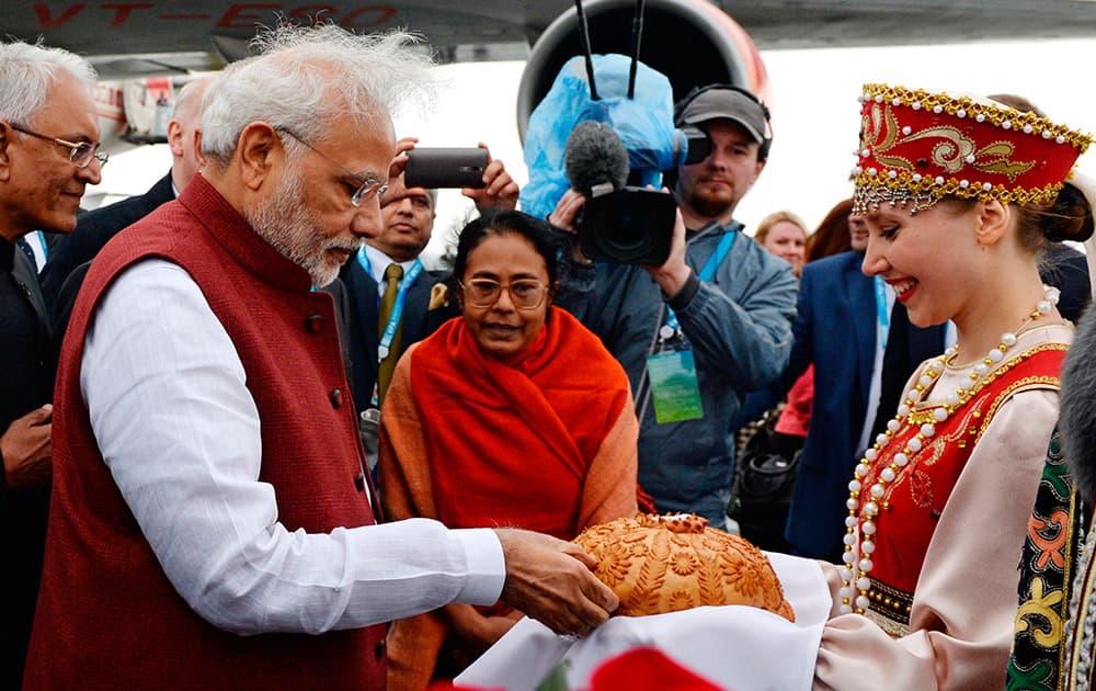 Prime Minister, Narenda Modi, tries traditional salt and bread upon arrival in Ufa, Russia.