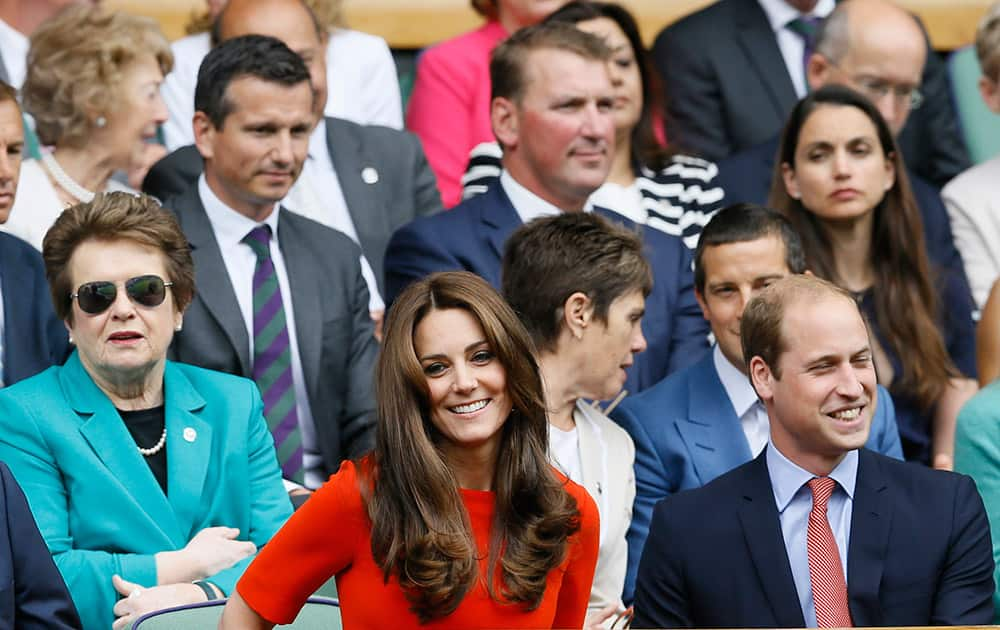 Britain's Prince William, the Duke of Cambridge and Kate, the Duchess of Cambridge sit on Centre Court, with former Wimbledon Champion Billie Jean King in background left, at the All England Lawn Tennis Championships in Wimbledon, London.