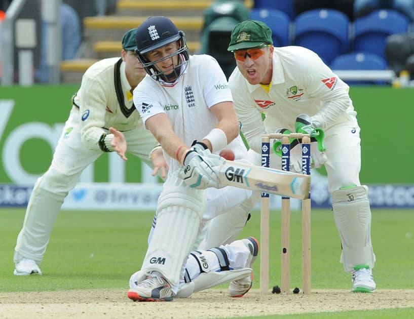 England's Joe Root plays a shot watched by Australia's wicket keeper Brad Haddin during day one of the first Ashes Test cricket match, in Cardiff, Wales.