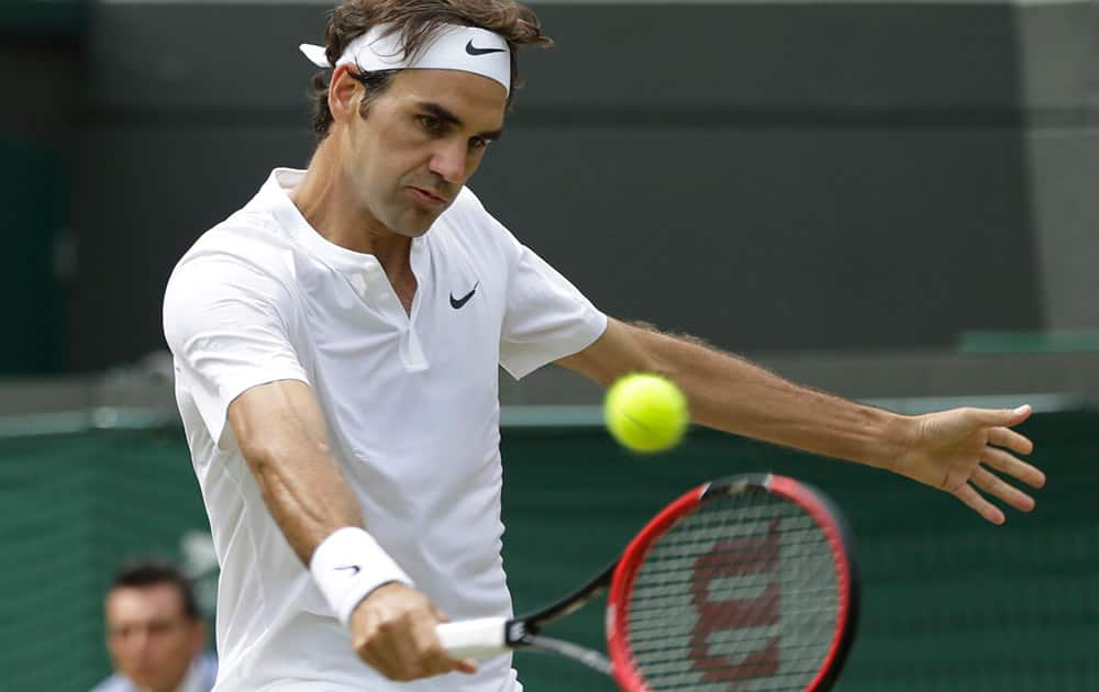 Roger Federer of Switzerland plays a return to Gilles Simon of France during the men's quarterfinal singles match at the All England Lawn Tennis Championships in Wimbledon, London.