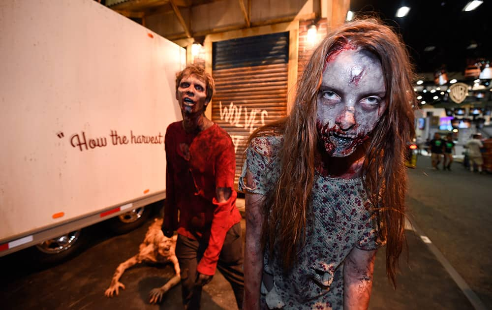 Zombies practices their walk at AMC's 'Walking Dead' booth before Preview Night at Comic-Con International held at the San Diego Convention Center, in San Diego.