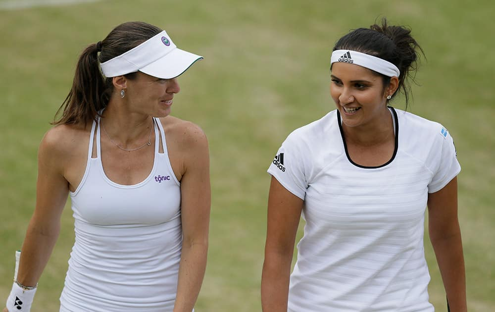 Martina Hingis from Switzerland and Sania Mirza from India talk between points during their doubles match against Casey Dellacqua from Australia and Yaroslava Shvedova from Kazakhstan at the All England Lawn Tennis Championships in Wimbledon, London.