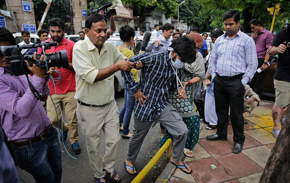 Puneet Kumar, accused of driving drunk in a hit-and-run car accident that killed an Australian student in Melbourne in 2008, is helped by his parents as they come out after being produced at a court in New Delhi, India