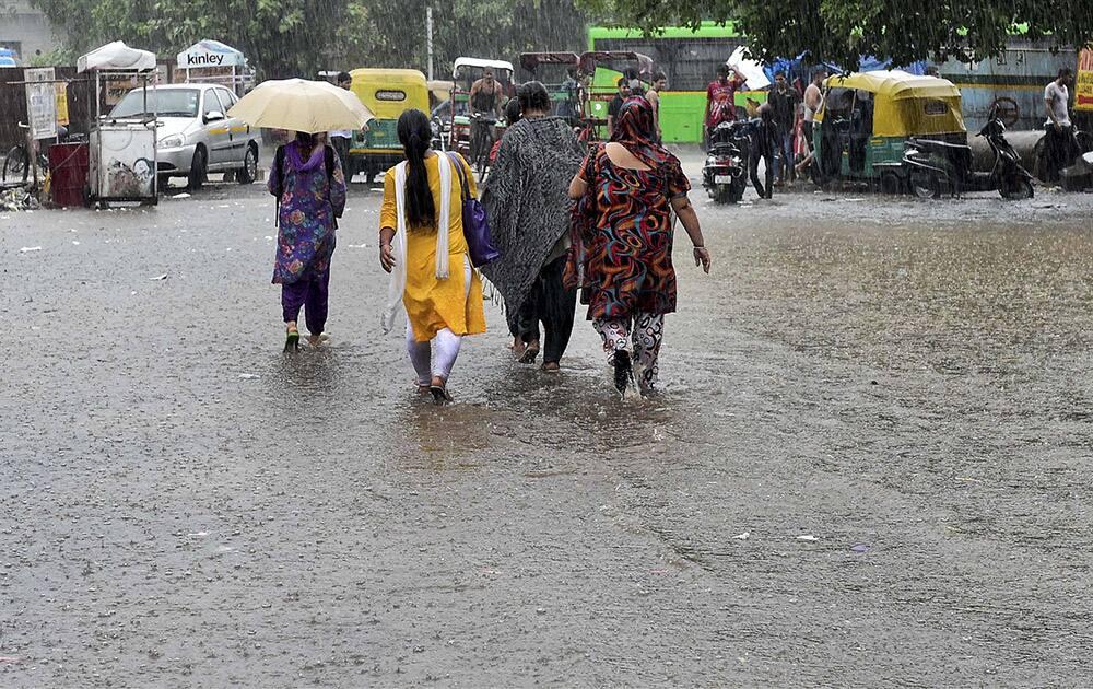 People walk on a water logged street in New Delhi.