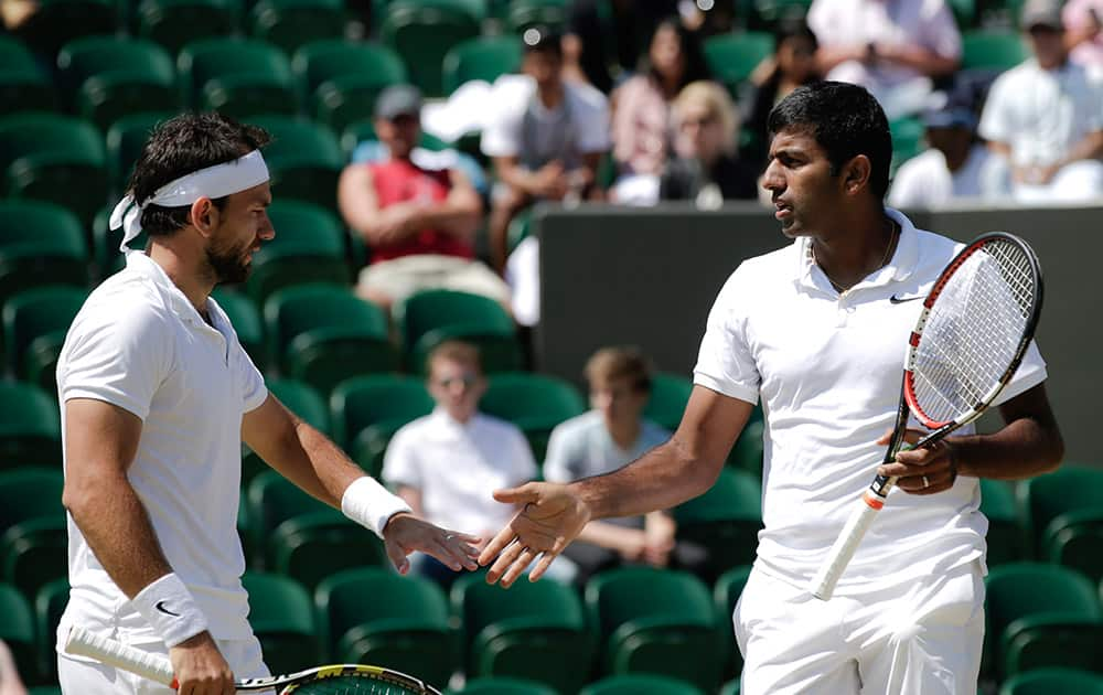 Rohan Bopanna and Florin Mergea of Romania talk between points during the men's semifinal doubles match against Jean-Julien Rojer of the Netherlands and Horia Tecau of Romania at the All England Lawn Tennis Championships in Wimbledon, London.