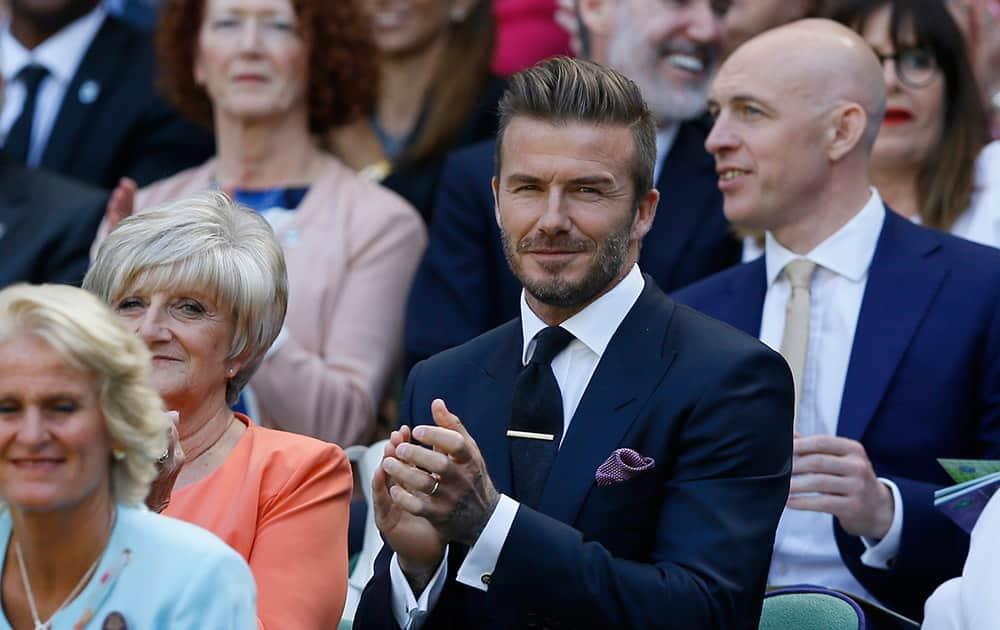 Former soccer player David Beckham and his mother Sandra, applaud during the women's singles semifinal match between Garbine Muguruza of Spain and Agnieszka Radwanska of Poland, at the All England Lawn Tennis Championships in Wimbledon, London.