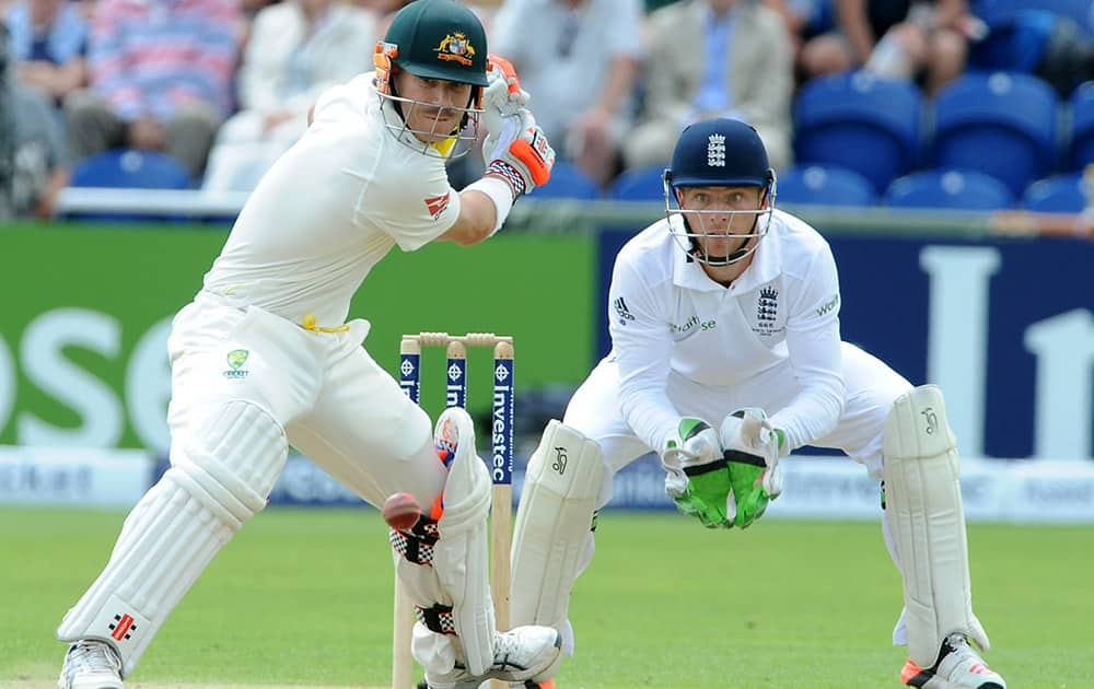 Australia's David Warner plays a shot watched by England's Jos Buttler during day two of the first Ashes Test cricket match, in Cardiff, Wales.