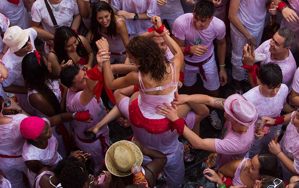 A girl is held by other revelers during the launch of the