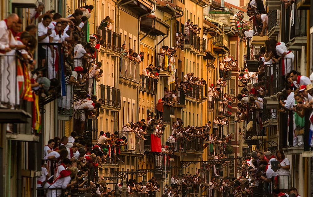 People watch as Jandilla fighting bulls and revelers run during the running of the bulls, at the San Fermin festival, in Pamplona, Spain.