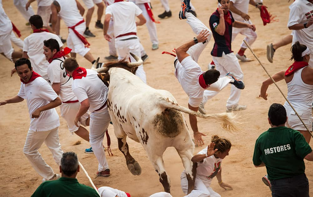 A runner is knocked by a steer during the second running of the bulls at the San Fermin Festival, in Pamplona, Spain.