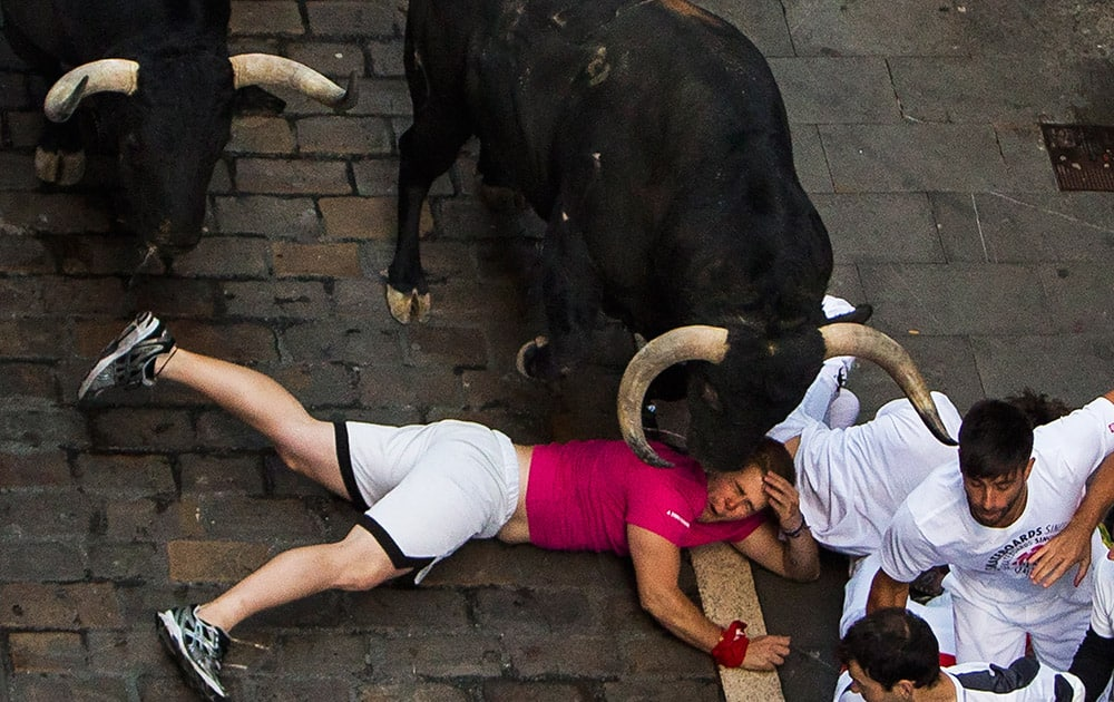 Victoriano del Rio fighting bulls run over revelers during the running of the bulls, at the San Fermin festival, in Pamplona, Spain.
