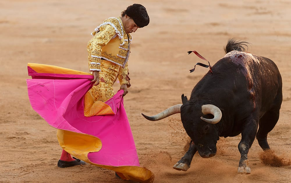 Spanish bullfighter Ivan Fandino performs with a Victoriano del Rio ranch fighting bull during a bullfight of the San Fermin festival in Pamplona, Spain.