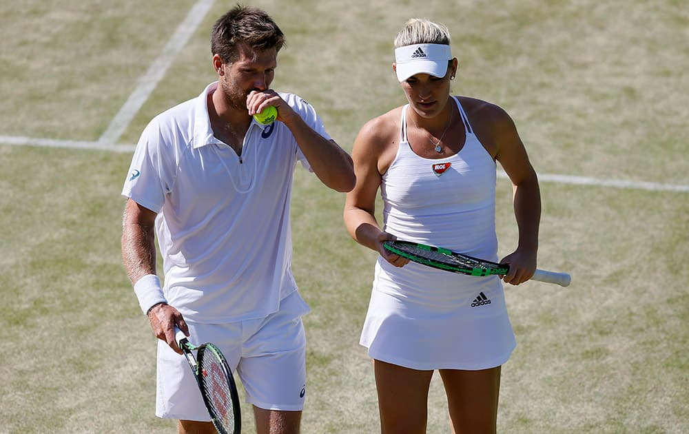 Alexander Peya of Austria and Timea Babos of Hungary talk between points during the mixed doubles quarterfinal match against Bruno Soares of Brazil and Sania Mirza of India at the All England Lawn Tennis Championships in Wimbledon.