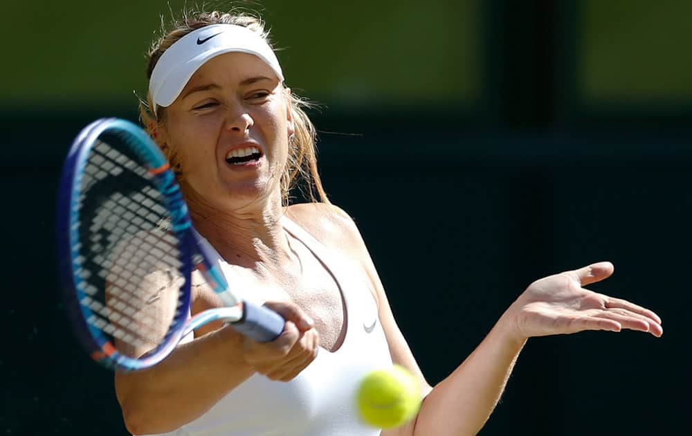Maria Sharapova of Russia returns a shot to Serena Williams of the United States, during the women's singles semifinal match at the All England Lawn Tennis Championships in Wimbledon, London.