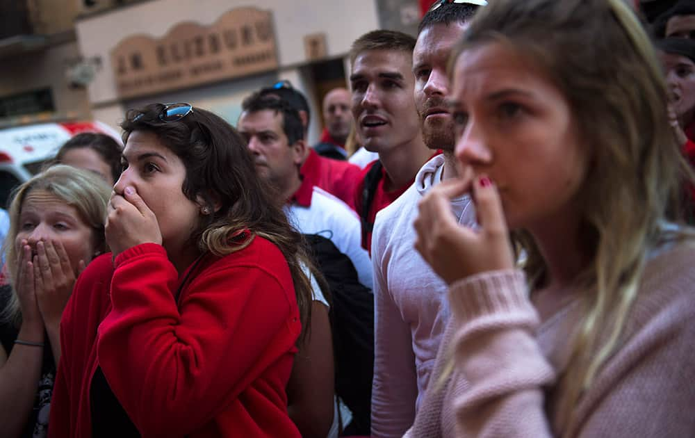 People make anxious while they watch ''Fuente Ymbro'' fighting bulls during the fourth running of the bulls, at the San Fermin Festival, in Pamplona, Spain.