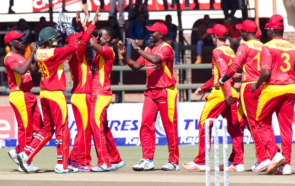Zimbabwean players celebrate the wicket of Indian batsman Kedar Jadhav after he was caught behind during the One Day International between the two teams in Harare, Zimbabwe.
