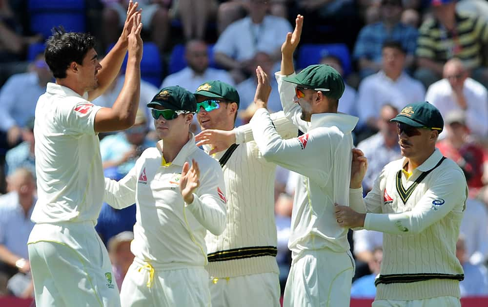 Australia's Mitchell Starc celebrates with teamates after bowling England's Alastair Cook caught Nathan Lyon for 12 runs during day three of the first Ashes Test cricket match, in Cardiff, Wales.