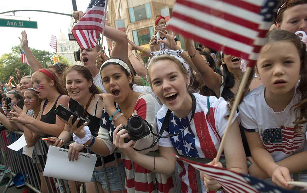 Fans cheer as the US Women's World Cup soccer champions parade through Broadway to City Hall, in New York.