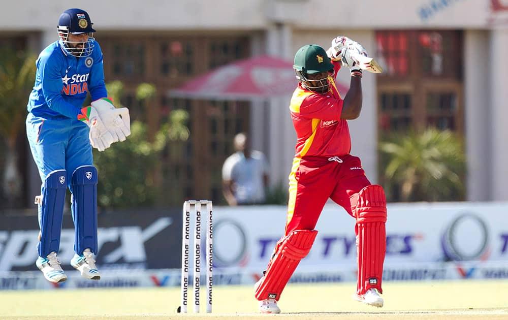 Zimbabwean batsman Hamilton Masakadza, right, plays a shot as Indian wicketkeeper Robin Utappa reacts during the One Day International in Harare, Zimbabwe.
