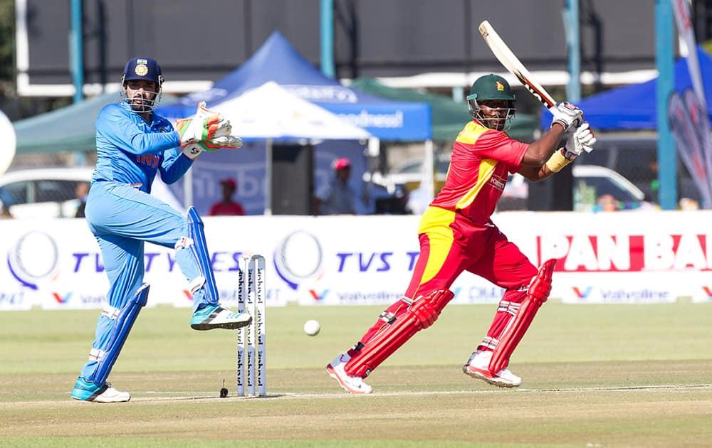 Zimbabwean batsman Hamilton Masakadza, right, plays a shot as Indian wicketkeeper Robin Utappa reacts during the One Day International against Zimbabwe in Harare, Zimbabwe.