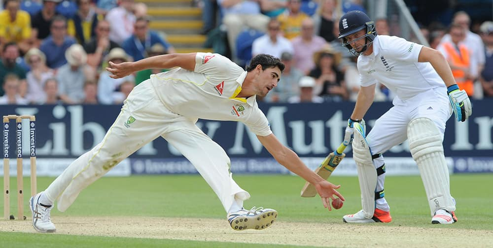 Australia's Mitchell Starc, left, reaches for the ball watched by England's Jos Buttler during day three of the first Ashes Test cricket match, in Cardiff, Wales.