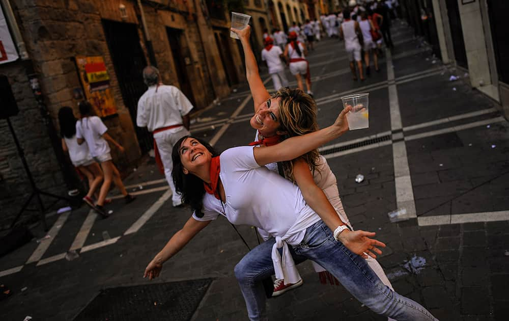 A couple dance on the street, at the San Fermin Festival, in Pamplona, Spain.