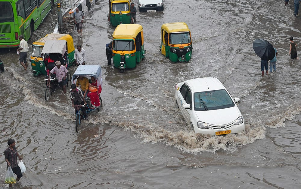 Traffic moves slowly at waterlogged roads near New Delhi Railway Station during rains.