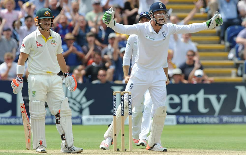 England's Jos Buttler celebrates after Australia's David Warner is trapped LBW by England's Moeen Ali for 52 runs during day four of the first Ashes Test cricket match, in Cardiff, Wales.