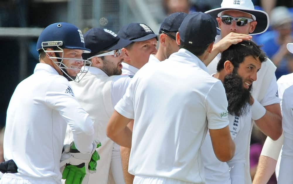 England's Moeen Ali is congratulated after trapping Australia's David Warner LBW for 52 runs during day four of the first Ashes Test cricket match, in Cardiff, Wales.