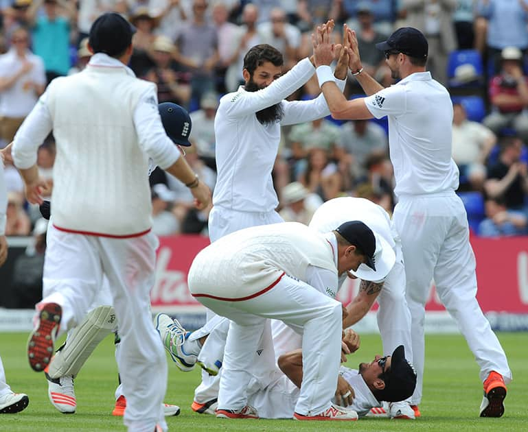 England's Moeen Ali celebrates with James Anderson after bowling Australia's Brad Haddin caught England's Alastair Cook for 7 runs during day four of the first Ashes Test cricket match, in Cardiff, Wales.