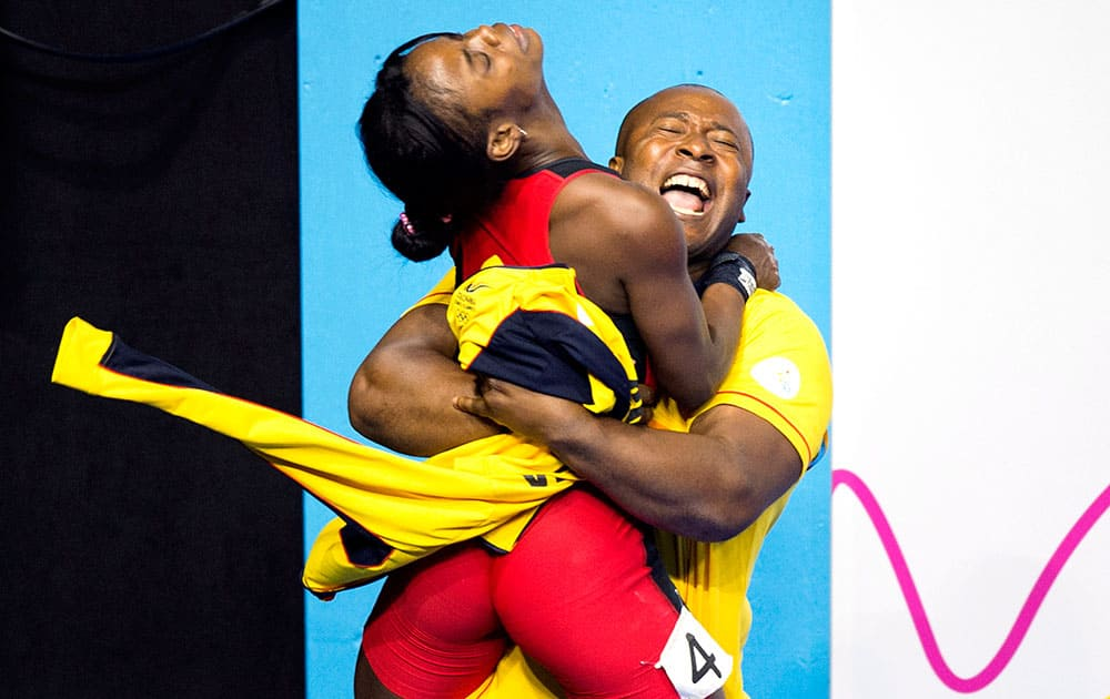 Ana Iris Segura Segura, left, of Colombia is hugged by her coach after winning the silver medal in women's 48kg weightlifting at the 2015 Pan Am Games in Toronto.