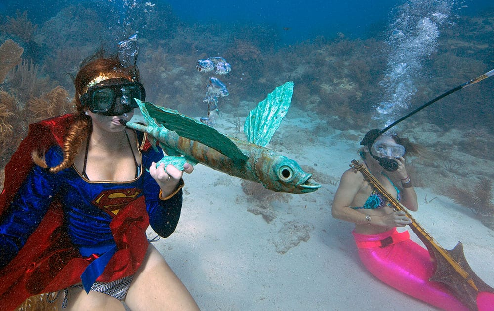 Kaitlin Goddard, left, costumed as superhero, blows through an artist's flying fish whistle, Saturday, July 11, 2015, during the Underwater Music Festival in the Florida Keys National Marine Sanctuary off Big Pine Key, Fla.