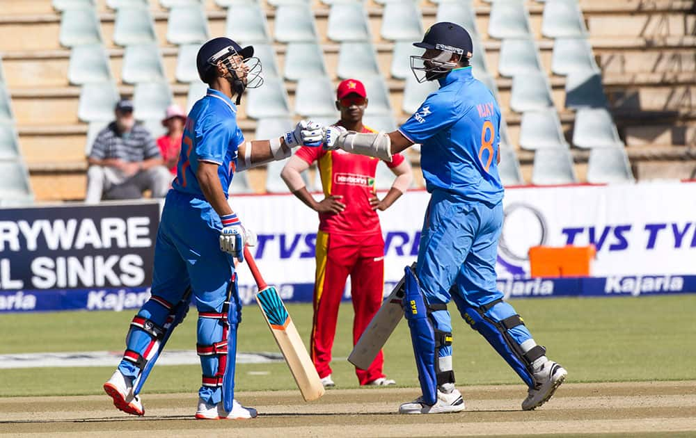Indian batsman Ajinkya Rahane,left, and Murali Vijay touch gloves in the second one-day international cricket match against Zimbabwe in Harare, Zimbabwe.