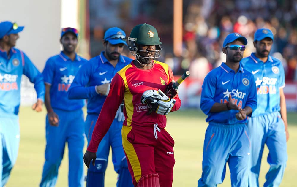 Zimbabwean and Indian cricket players walk off the pitch after the match on the second day of the One Day International cricket match between the two teams in Harare, Zimbabwe.