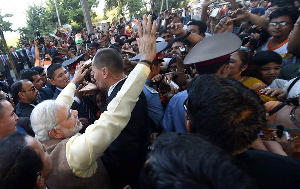 Prime Minister Narendra Modi waves to people after unveiling the Mahatam Gandhi statute in Bhishkek.