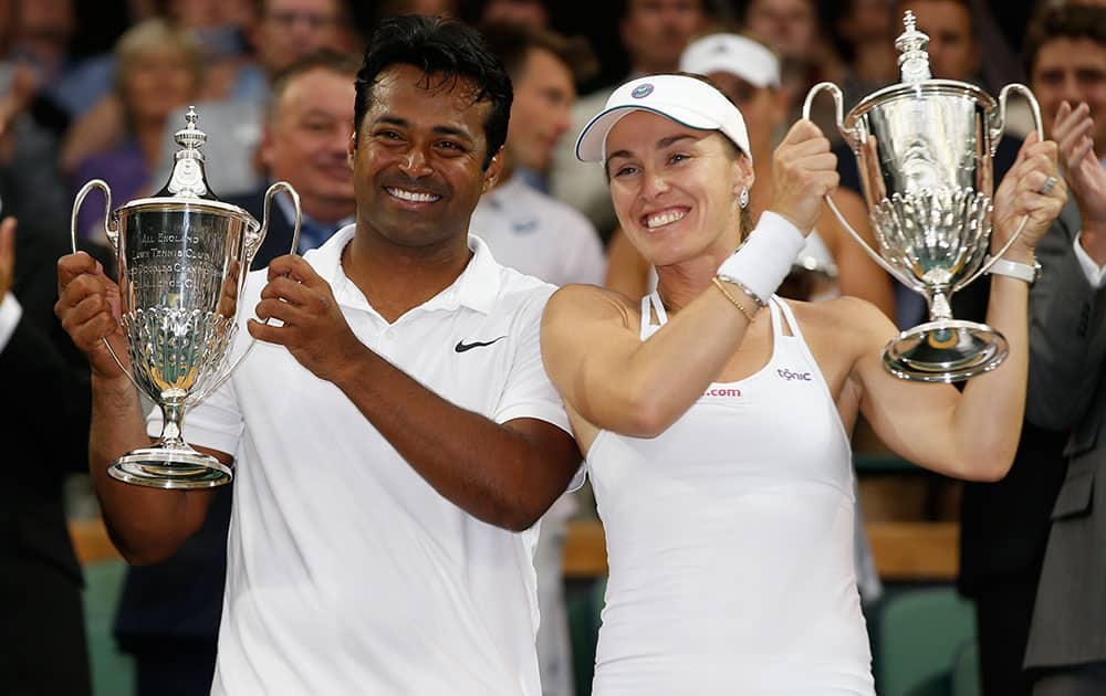 Leander Paes of India, left, and Martina Hingis of Switzerland hold up the trophies after winning the mixed doubles final against Alexander Peya of Austria and Timea Babos of Hungary at the All England Lawn Tennis Championships in Wimbledon, London.