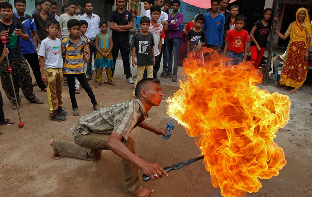 Residents gather to watch as an Indian man displays his fire stunt skills before media in Ahmadabad, India